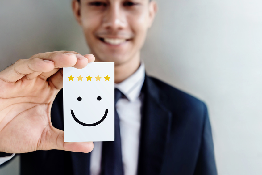 Customer Experience Concept, Happy Businessman holding Card with Smiley Face and Five Star Rating for his Satisfaction